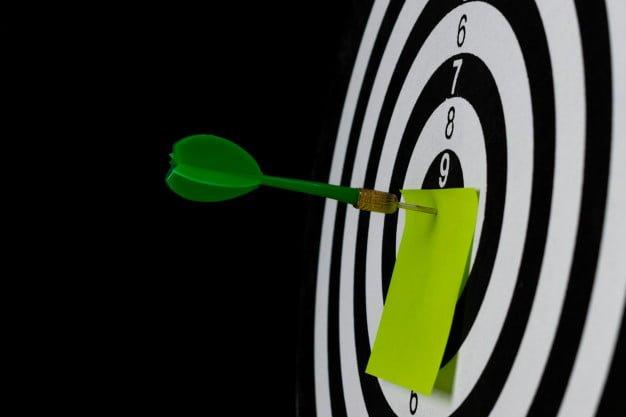 green-dart-arrow-hitting-target-center-dartboard-with-post-it-paper-text_101840-278